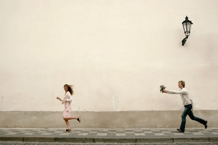 Side shot of man holding a bouquet of flowers chasing after his girlfriend down the street photo