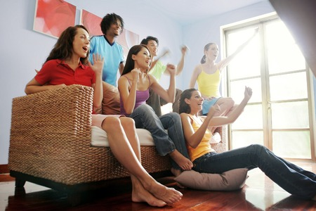 home entertainment: A group of friends cheering while watching football match on the television