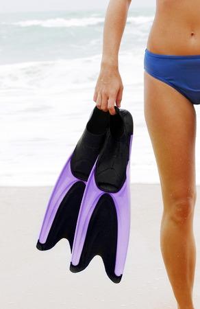 bikini bottom: La mitad-shot de una dama en la parte inferior del bikini azul que sostiene un par de aletas