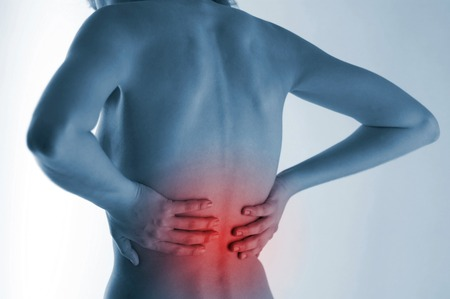throbbing: Back shot of a woman touching her aching back