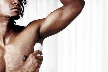 An African American man applying an antiperspirant product on his underarm