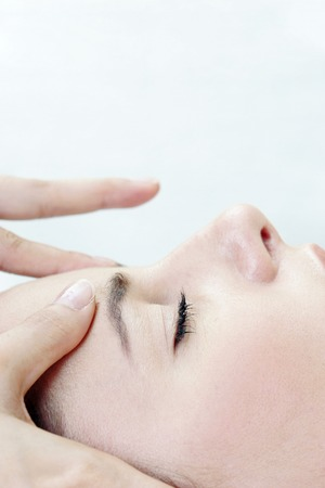 spoiling: Side view of hands massaging a ladys forehead