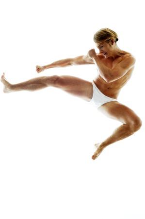 inner wear: A shirtless man in white underwear kicking while jumping