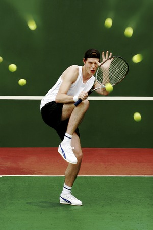 A man using his tennis racquet to defend himself from being hit by the tennis balls