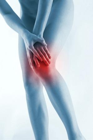 throbbing: Waist down shot of a woman touching her aching knee Stock Photo