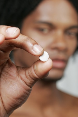 An African American man showing a pill to the camera Stock fotó