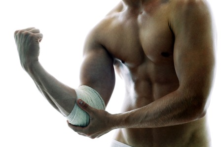 body built: A shirtless muscular man with a bandage on his elbow Stock Photo