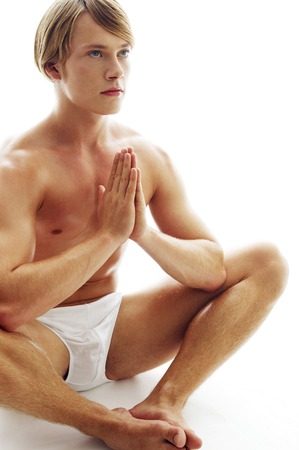 A shirtless man in white underwear sitting on the floor praying photo