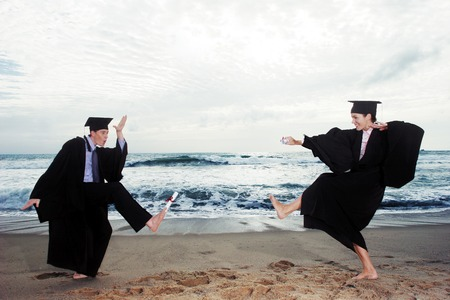 fresh graduate: A guy and lady in a robe and mortar board playing on the beach