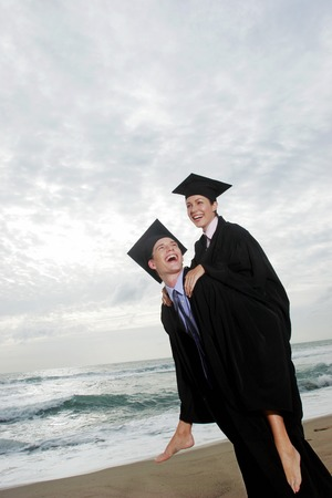 A guy and his girlfriend rejoicing their graduation by giving her a piggy back ride photo