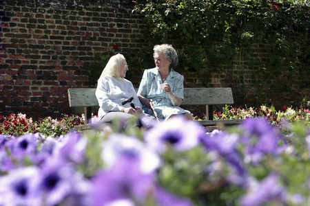 Two old women sitting on a bench in the garden talking photo