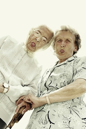 Low angle view of two old women showing their tongues at the camera photo