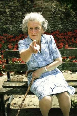 An old woman with walking stick scolding photo