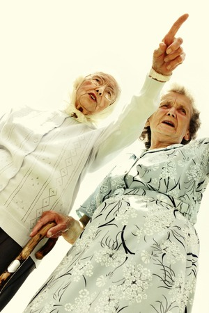 Low angle view of an old woman showing something to her friend who is holding a walking stick photo