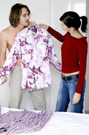 A lady helping her boyfriend to choose clothes photo