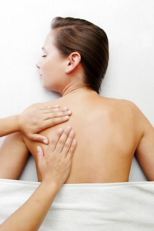 spoiling: A hand massaging a ladys back Stock Photo
