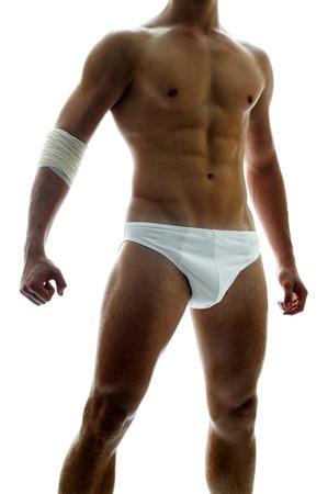 suo: Spalla gi� tiro di un uomo muscoloso shirtless in biancheria intima bianca con una benda sul gomito