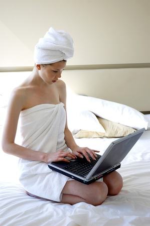 hair wrapped up: A woman with her body and her hair wrapped up in towel sitting on the bed using laptop