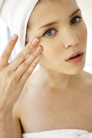 white cream: A woman with her hair and body wrapped up in towel applying under eye cream