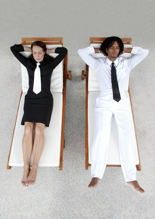 A lady in black suit and white tie and an African American man in white suit and black tie resting on the chairs photo