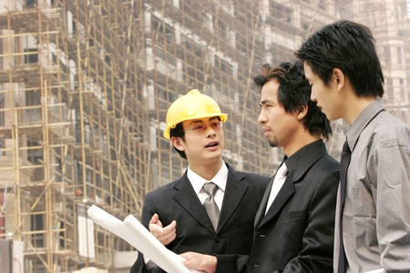 bespectacled man: A bespectacled man in business suit and protection helmet talking to two men in formal wear