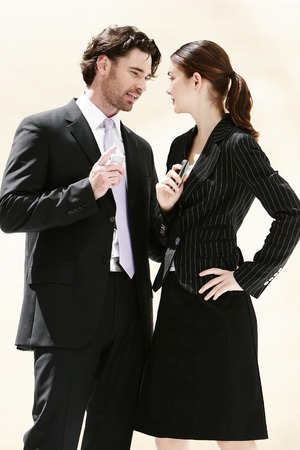 A man and woman standing face to face with each holding a hand phone photo