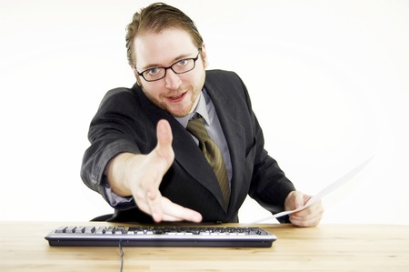 bespectacled man: A bespectacled man in business suit reaching out his hand for a handshake Stock Photo