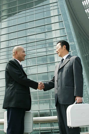 bespectacled man: A bespectacled man in business suit shaking hands with a bald man in business suit
