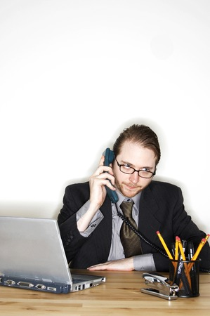 bespectacled man: A bespectacled man sitting at his desk talking on the phone