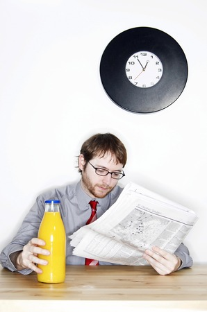 bespectacled man: A bespectacled man reading newspaper while having a bottle of orange juice for his lunch