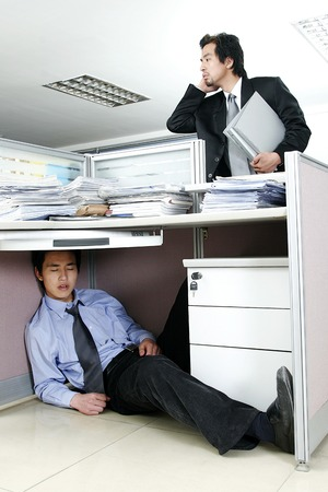 A guy searching for his friend who is sitting under his desk sleeping photo