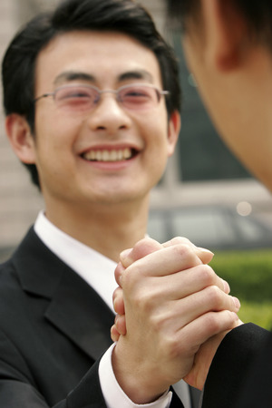 bespectacled man: A bespectacled man hand grasping with a guy