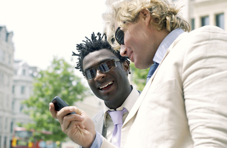 A guy in white suit and sunglasses showing his African American friend the messages in his hand phone                                photo