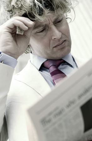 A man pushing his sunglass up on his forehead while reading newspaper Stock Photo - 26132374