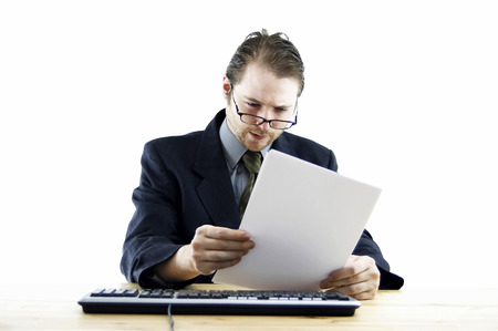 bespectacled man: A bespectacled man in business suit sitting at his desk reading some notes