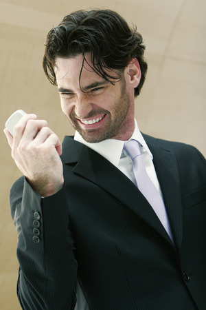 overjoyed: An overjoyed looking guy smiling while grasping his hand phone Stock Photo