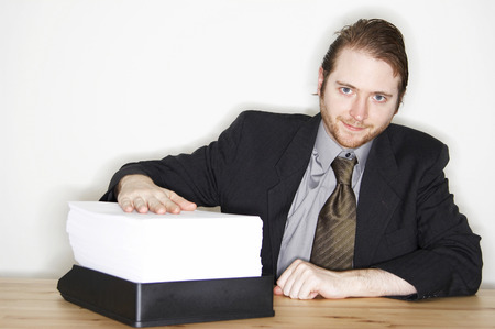 he: A man in business suit showing the stack of paperwork he has to finish