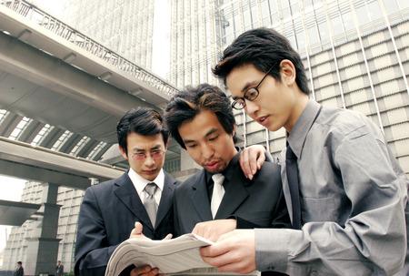 Three men in formal wear sharing a newspaper