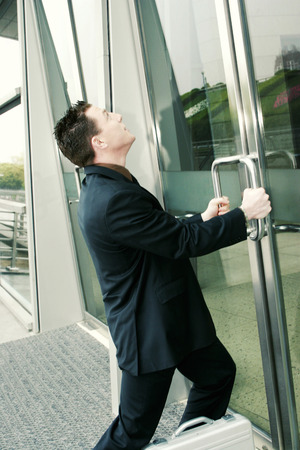 An Asian guy in business suit trying to open a locked door photo