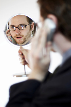 he: Back shot of a man looking at a mirror he is holding while talking on the hand phone
