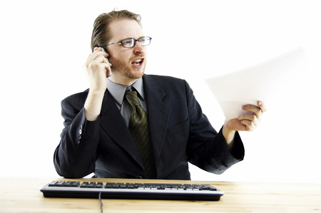 bespectacled man: A bespectacled man passing a paper while talking on his hand phone Stock Photo