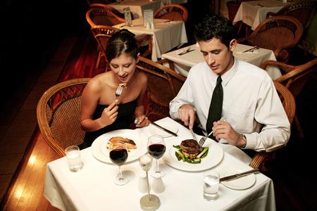 Ein Paar in Abendessen zu tragen feiert ihr Jubiläum durch den Verzehr im Restaurant