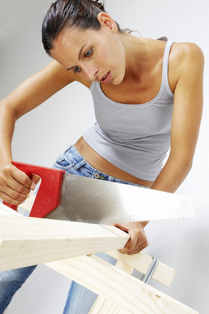 A woman sawing a wood photo