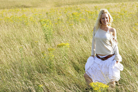 long skirt: A woman standing on the prairie holding her long skirt