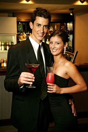 dinners: A couple in dinners wear standing together holding cocktails Stock Photo