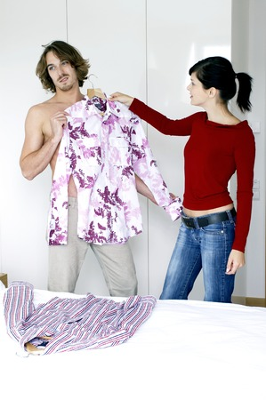 A guy showing his uninterested face towards the clothes his girlfriend chose photo