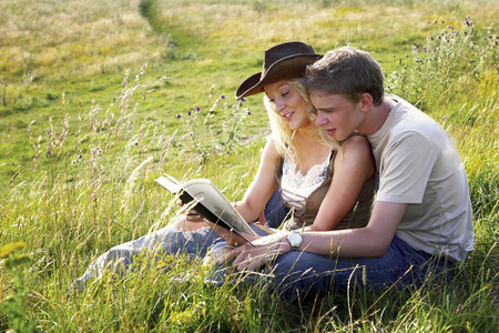 A couple sitting on the grass reading book photo