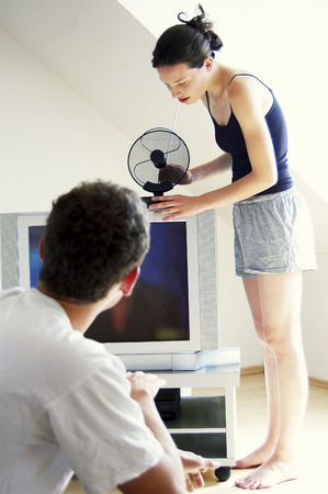clearer: A man adjusting the indoor antenna for a clearer vision while her boyfriend is watching