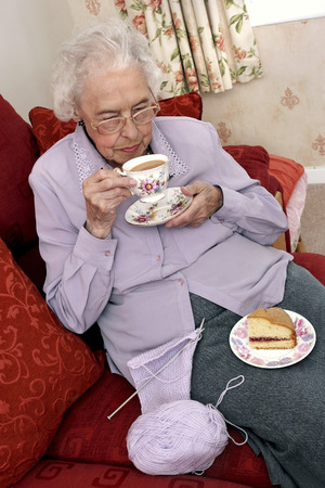 An old bespectacled woman stop knitting for her tea time photo