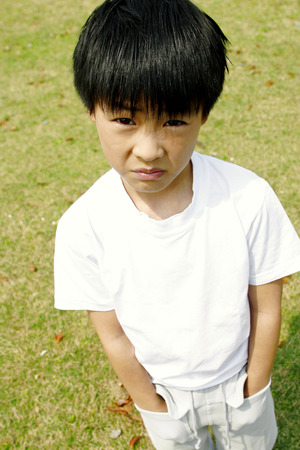 glum: A boy standing on the field with his hands in the pockets